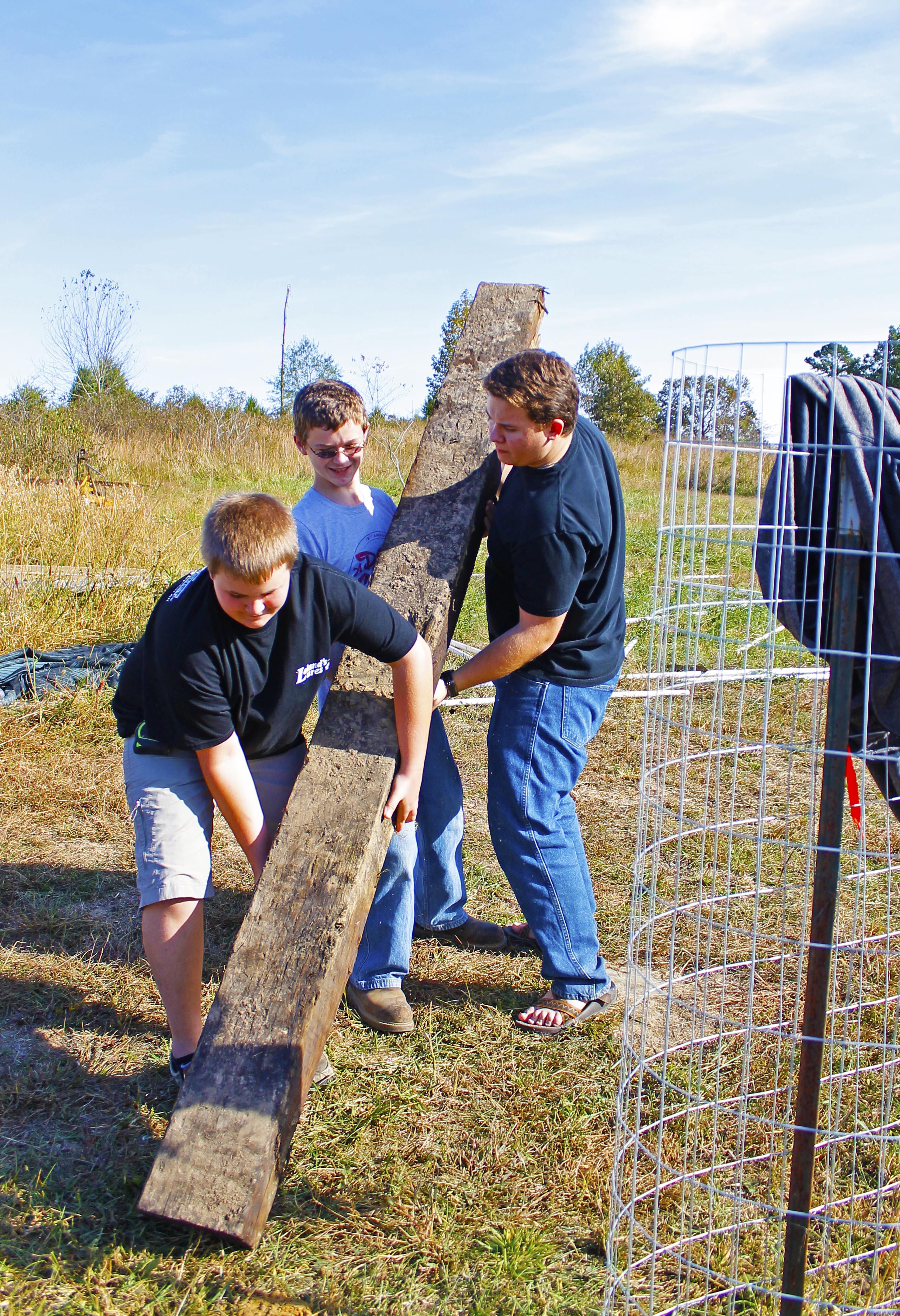 Several visiting youth put finishing touches on a fence while learning about global agricultural practices.