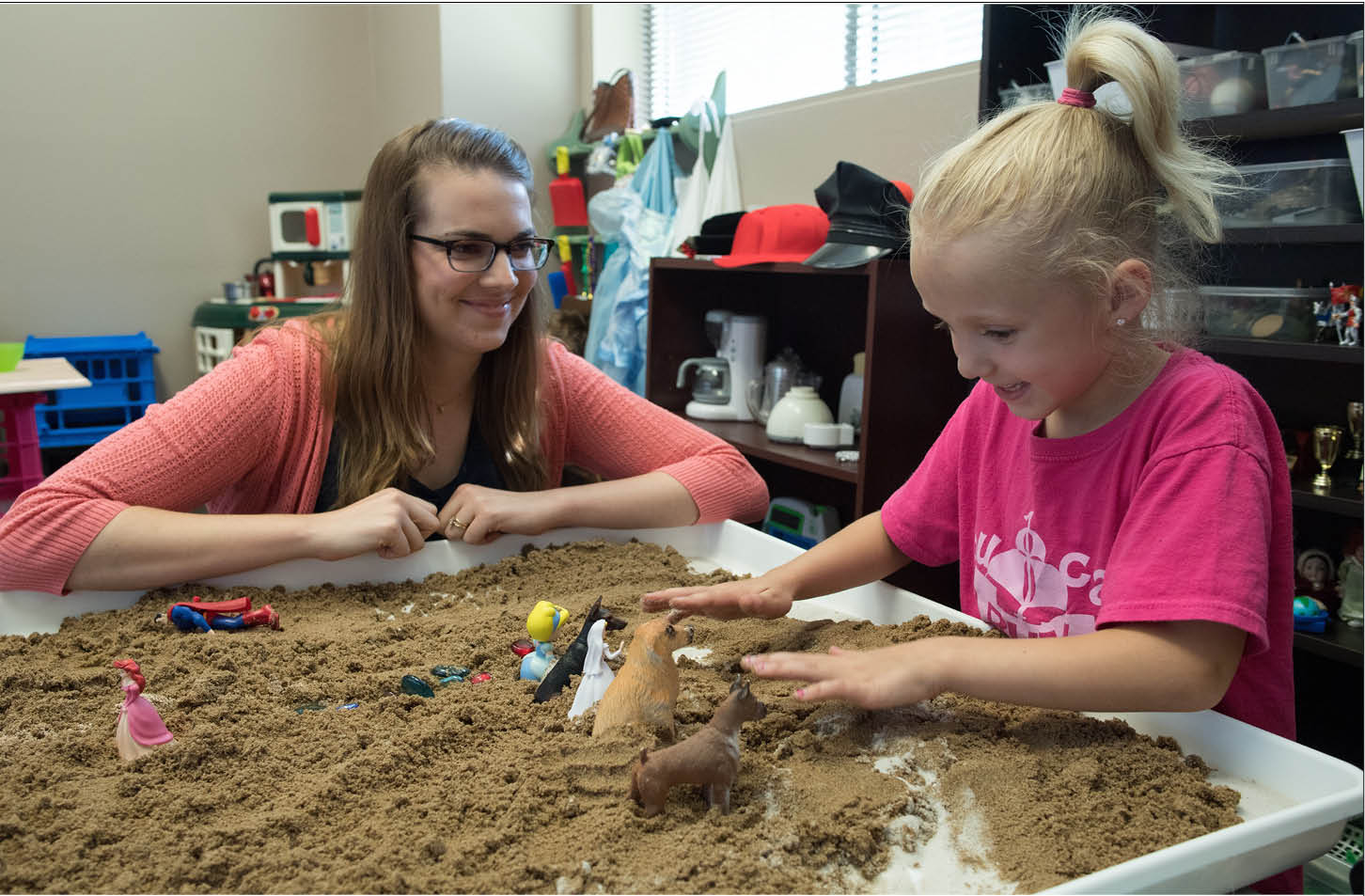 This is a photo of a school counselor using play therapy with sand