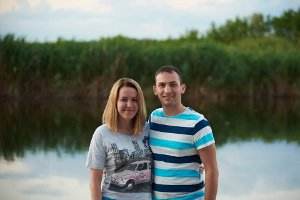 Dmytro and his wife smiling for a photo in front of a body of water
