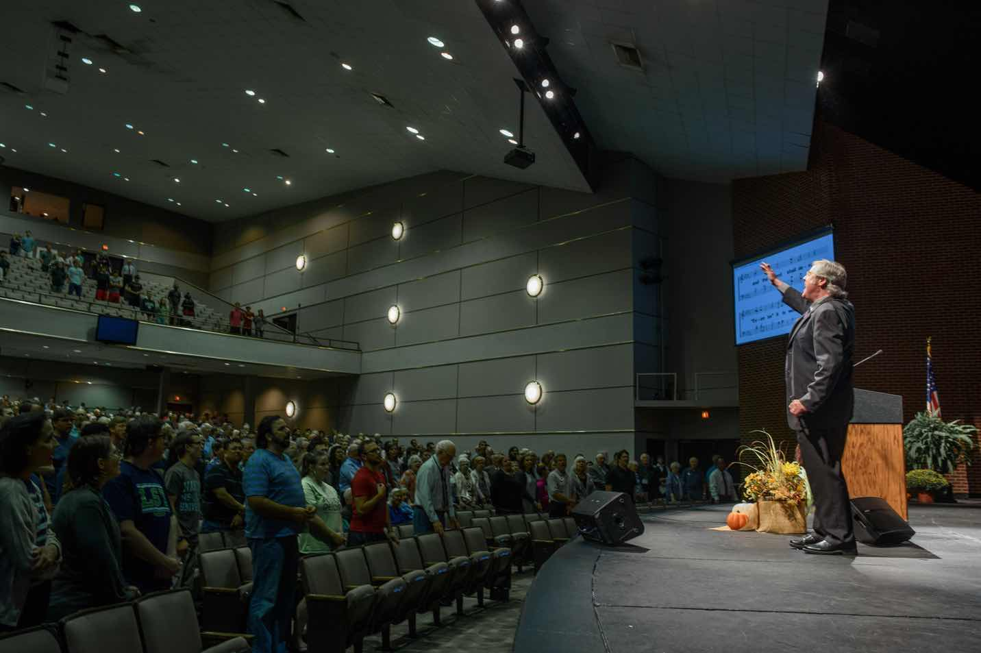 A photo of an audience in the Benson Auditorium audience singing at the 2016 annual Bible Lectureship.