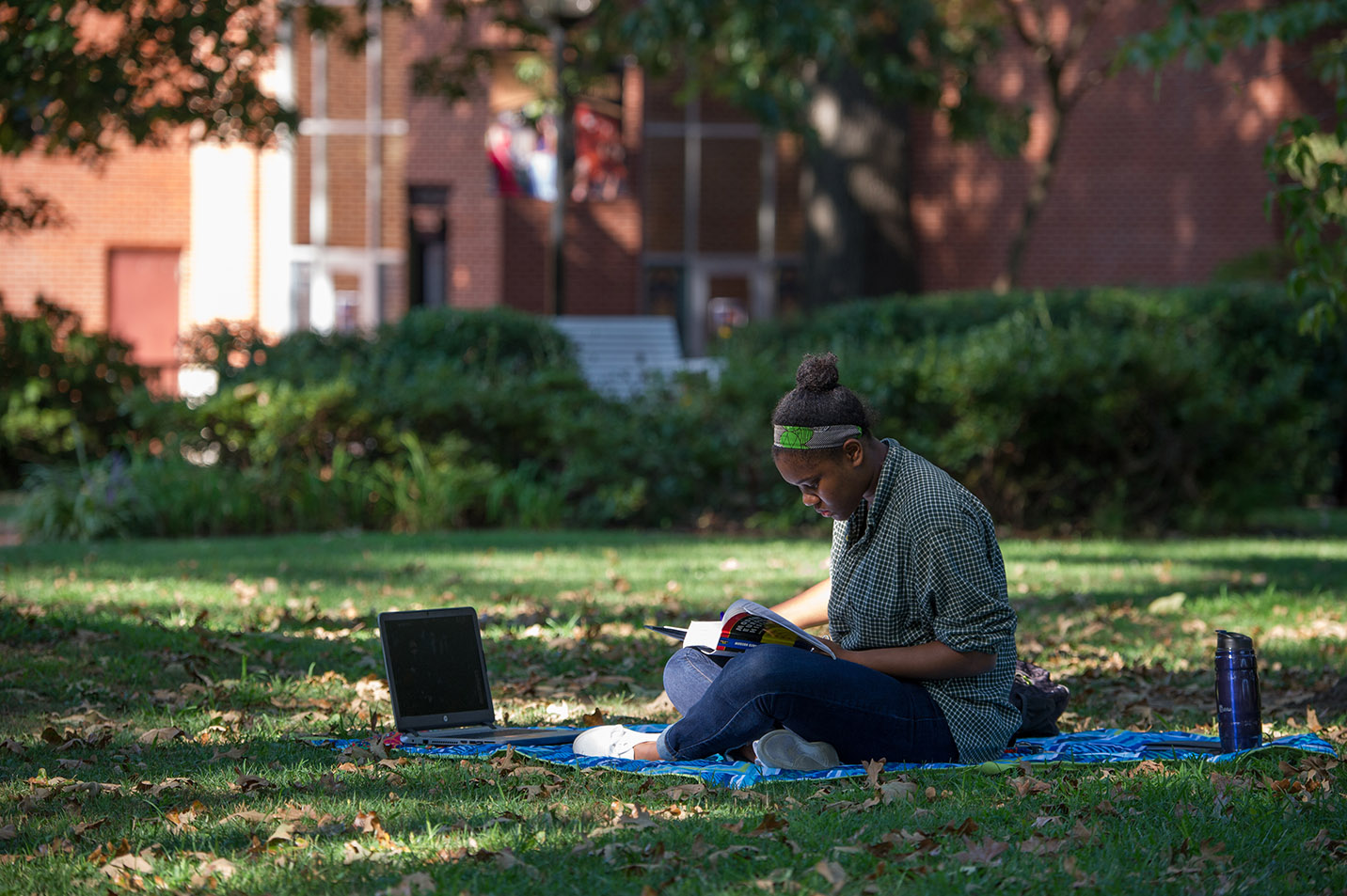 This is a photo of a student studying on the front lawn.